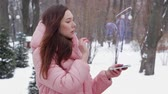 hotéis : Beautiful young woman in a winter park interacts with HUD hologram with big balloon. Red-haired girl in warm pink clothes uses the technology of the future mobile screen Stock Footage