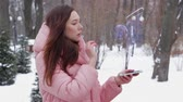 Beautiful young woman in a winter park interacts with HUD hologram with TIR Truck. Red-haired girl in warm pink clothes uses the technology of the future mobile screen