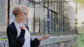 estratégico : Curly young woman in glasses interacts with a hud hologram with text Algorithm. Blonde girl in white and black clothes uses technology of the future mobile screen Vídeos