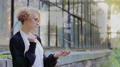 simulatie : Curly young woman in glasses interacts with a hud hologram with text Simulation software. Blonde girl in white and black clothes uses technology of the future mobile screen