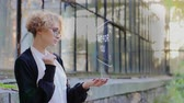 filozofie : Curly young woman in glasses interacts with a hud hologram with text Time for you. Blonde girl in white and black clothes uses technology of the future mobile screen
