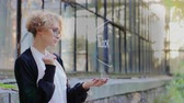 identifier : Curly young woman in glasses interacts with a hud hologram with text Unlock. Blonde girl in white and black clothes uses technology of the future mobile screen Vidéos Libres De Droits