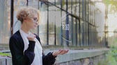 simulatie : Curly young woman in glasses interacts with a hud hologram with text VR 360. Blonde girl in white and black clothes uses technology of the future mobile screen Stockvideo