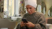 hold : Smiling lady takes care of her hair and solves problems using a smartphone. Beautiful happy woman with a towel on her head and a mobile phone is waiting for hair treatment in a beauty salon