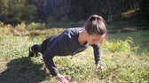 push ups : Young girl doing outdoor exercise. Girl doing push-ups in the park. Outdoor training girl