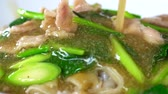 stir fried vegetables : Chef pouring soup to Fried noodles with pork and kale in gravy sauce. Stock Footage