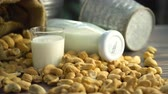 Still life of cashew milk and toasted cashew nuts on table, Shot in studio, movement camera, selective focus and free space for text. Good healthy food ideas concept.