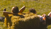 bliss : A guy and a girl are lying on the hay Stock Footage