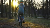 cyklista : Little boy riding the bicycle in the park, sundown park, slow motion
