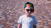 pflastersteine : Young boy in sunglasses and a cap walking down the street, Child 6 year old kid walking, slow motion Stock Footage