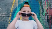 grafiti : A cool 5 year old boy in a cap and sunglasses posing on the camera near the wall with graffiti, a child in sunglasses takes them off and clothes them back Dostupné videozáznamy