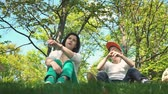 soru : Mom and son are looking into the distance and talking while sitting in the park on the green grass, family holiday