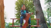 lad : Happy smiling boy on a wooden swing in the form of an airplane in a park in the sunlight. A child is having fun on a swing