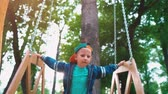 lad : Happy smiling boy on a wooden swing in the form of a throne in a park in the sunlight. A child is having fun on a swing Stock Footage