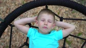 детский : A blue-eyed, 5-year-old boy in a blue T-shirt dreams with his eyes closed, lying on a round swing. A child smiles while thinking about a pleasant hovering above the ground on a swing