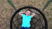 детский : The blue-eyed five-year-old boy in blue t-shirt lies on a round swing with his hands behind his head, looks at the camera and smiles, the child is resting, lying on the swing