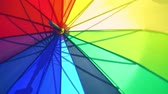 аксессуар : An open large umbrella of rainbow color turns, a colorful umbrella rotates in an open view Стоковые видеозаписи