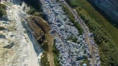 consumo : Fly about garbage dump. Excavator working on the ground. Aerial view. Vídeos