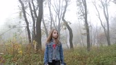Little European girl with a long hair, blue jacket, black pants, sneakers and blue eyes. A frightened little child is walking through the foggy deserted forest. Loneliness. Steady cam front shot.