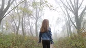 Little European girl with a long hair, blue jacket, black pants, sneakers and blue eyes. A frightened little child is walking through the foggy deserted forest. Loneliness. Steady cam behind shot.