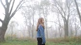 Little European girl with a long hair, blue jacket, black pants, sneakers and blue eyes. A frightened little child is standing in the foggy deserted forest. Loneliness. Steady cam fly around shot. Dostupné videozáznamy