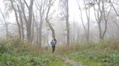 Little European girl with a long hair, blue jacket, black pants, sneakers and blue eyes. A frightened little child is running through the foggy deserted forest. Loneliness. Steady cam front shot.