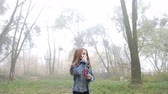 Little European girl with a long hair, blue jacket, black pants, sneakers and blue eyes. A frightened little child is walking through the foggy deserted forest and talking cell phone. Loneliness. Steady cam front shot. Dostupné videozáznamy