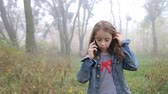 Little European girl with a long hair, blue jacket, black pants, sneakers and blue eyes. A frightened little child is walking through the foggy deserted forest and talking cell phone. Loneliness. Steady cam front medium shot.
