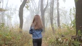Little European girl with a long hair, blue jacket, black pants, sneakers and blue eyes. A scarried little child is running away through the foggy deserted forest. Loneliness. . Steady cam back shot.