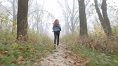 Little European girl with a long hair, blue jacket, black pants, sneakers and blue eyes. A frightened little child is running through the foggy deserted forest. Loneliness. Steady cam behind shot.