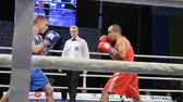 átlyukasztás : LVIV, UKRAINE - November 14, 2017 Boxing tournament. Midweight boxers fight in boxing ring on tournament. Steadycam shot.