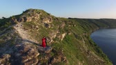 Aerial flight away from couple in love standing in cliff edge near water. Woman in amazing red dress. Man in black. Sunset. 4K
