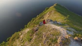 Aerial flight above couple in love standing in cliff edge near water. Woman in amazing red dress. Man in black. Sunset. 4K
