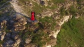 Aerial flight around couple in love standing in cliff edge near water. Woman in amazing red dress. Man in black. Sunset. HD Dostupné videozáznamy