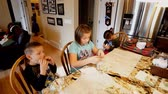 biscoitos : Children eating cookies and wrapping some for gifts Stock Footage
