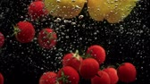 kalori : Cherry tomatoes and red yellow paprika bell peppers falling into water with air bubbles slowmotion Stok Video