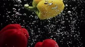 ketçap : Ripe bell peppers falling into water black background Stok Video
