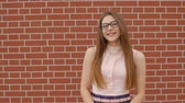 rayonnant : Young student girl in glasses laughs against a brick wall background