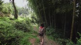wandelstok : Travel girl with bag walks along path in tropical park of tropical plants, palms, bamboo plantation