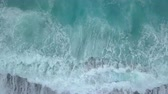 Aerial top view of sea waves foaming and splashing, big waves from above rolling and breaking on empty ocean beach. Zoom out drone shot Stockvideo