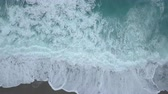 Aerial top view turquoise sea waves break on empty sand beach. Clean sea waves from birds eye view, ocean waves reaching shore and splashing from above Stockvideo