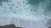 Aerial top view turquoise sea waves break on empty sand beach. Clean sea waves from birds eye view, ocean waves reaching shore and splashing from above Wideo