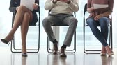 concorrentes : Ready to get new career. Group of three young businesspeople sitting on chairs in office, waiting and going for job interview, feeling nervous. Body language. Close up of legs. Job search concept
