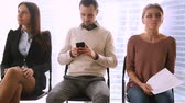 três : Business people group sitting in row on chairs, three job applicants await for their turn in queue, waiting for job interview concept, man and two women preparing for audition, feeling stressed bored Stock Footage