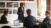 African-american businessman giving presentation to caucasian partners with flipchart, leader explaining team new project plan on whiteboard, startupper making offer to investors, business coaching Стоковые видеозаписи