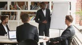 African businessman discussing presentation with clients in boardroom, business coach asking questions standing near whiteboard at seminar, black leader discussing project with caucasian partners