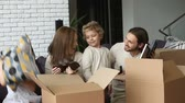 relocating : Smiling family with small son and daughter unpacking boxes together sitting on couch in modern cozy living room, happy parents playing with kids unboxing belongings after relocation into new home