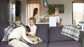 Happy family couple spending time with children, having fun with small kids in modern cozy big living room, father playing pillow fight with son on sofa, mother and daughter standing at dining table Стоковые видеозаписи
