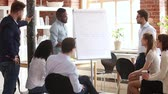 apresentador : Male african speaker giving flipchart presentation explaining project growth graph training sales team, black coach trainer speaking about financial result at corporate group office meeting seminar Vídeos