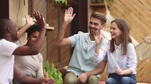 slib : Happy diverse friends students group giving high five celebrating multi-ethnic friendship at meeting outdoor, young multicultural people join hands show unity support having fun making deal together